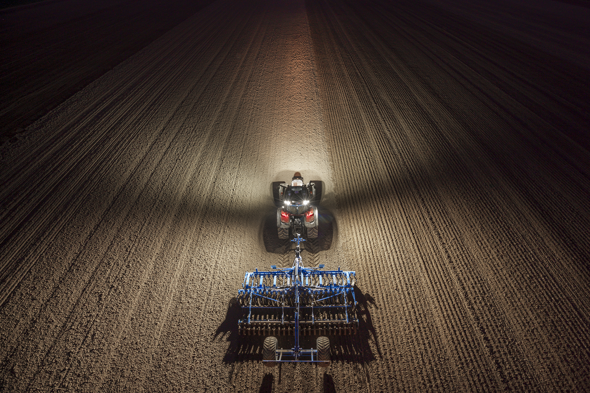 valtra t4 series tractor on the field at night with working lights